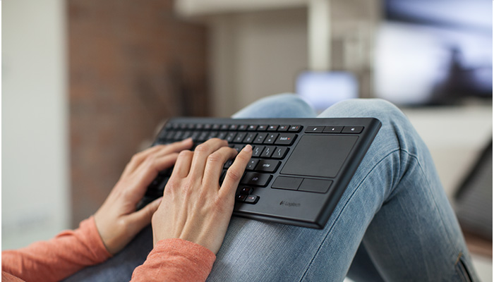 Person holding K830 keyboard in living room setting